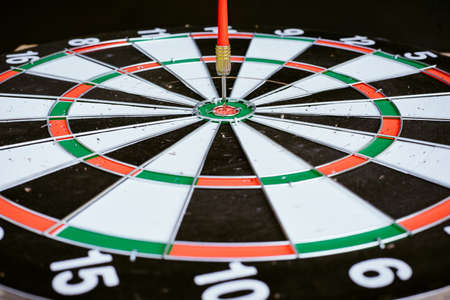 Close up Red dart arrow hitting on the center  dartboard, Marketing target success or the winner, on black background