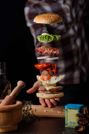 man carrying a delicious hamburger with flying ingredients