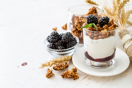 jar: Breakfast - granola, yogurt, berries, wheat, white wood background, copy space