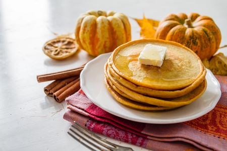 calabaza: Crepes de la calabaza en un plato blanco con mantequilla y miel, la madera de fondo blanco Foto de archivo