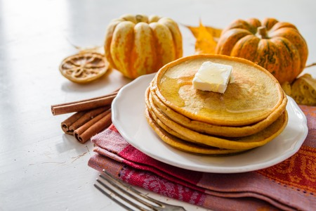 dynia: Pumpkin pancakes on white plate with butter and honey, white wood background