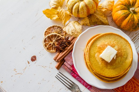 Pumpkin pancakes on white plate with butter and honey, white wood background