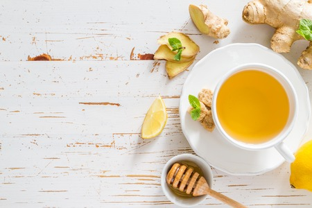 Ginger tea and ingredients on white wood background, copy space