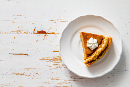 Pumpkin pie, white wood background, top view