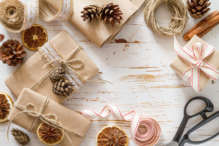 Christmas presents in rustic wrap, white wood background, top view