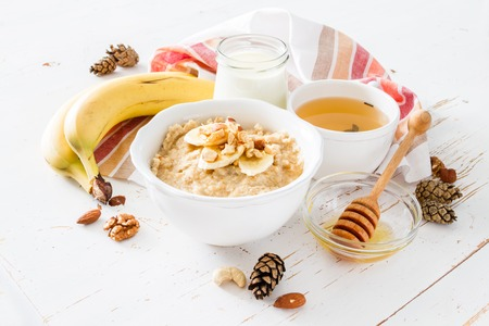Autumn oatmeal in white bowl banana honey yogurt white wood background Фото со стока