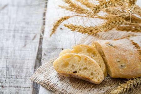 life loaf: Ciabatta wheat rustic wood background, closeup, copy space