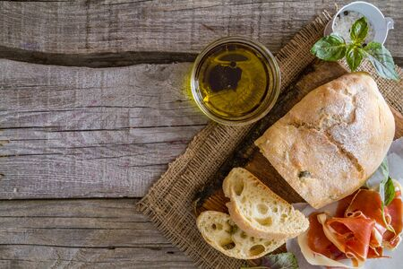 pain: appetizer - ciabatta ham basil tomato, rustic wood background, top view