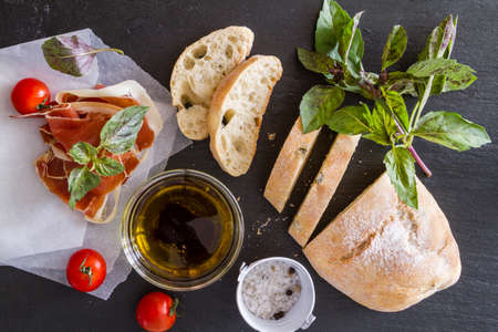ciabatta: appetizer - ciabatta ham basil tomato, rustic wood background, top view