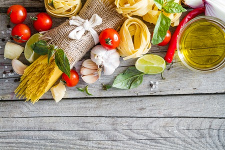 italy food: Pasta and ingredients tomato, garlic, onion, oil, basil  on rustic background