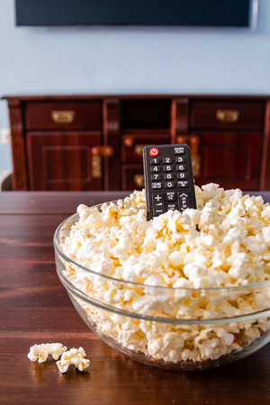bowls of popcorn: Popcorn in glass bowl and remote control on wood background