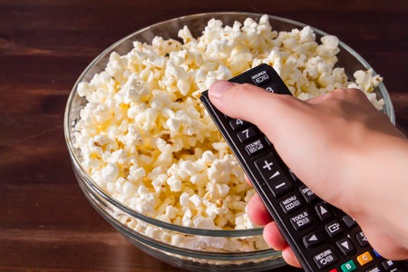 bowls of popcorn: Hand holding remote control, popcorn, wood background