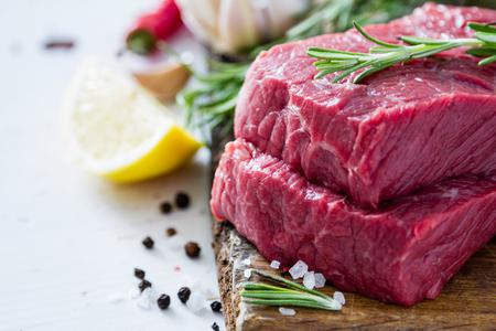 carnes rojas: Raw romero carne en rodajas en el fondo de madera Foto de archivo