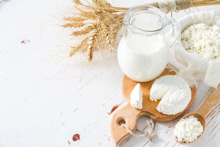 Selection of dairy products and wheat on white wood background