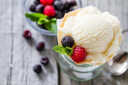 helados: Helado en cono de la galleta fondo de madera r�stica