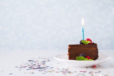 frutas divertidas: Birthday chocolate cake with candle, light blue background, bokeh Foto de archivo