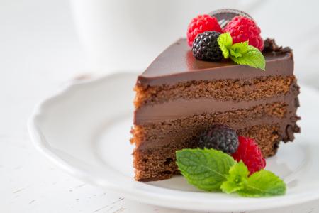 rebanada de pastel: Rebanada de pastel de chocolate en un plato blanco bayas de menta, fondo blanco