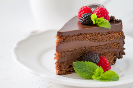 Schokoladenkuchenscheibe auf weißer Platte Minze Beeren, weißem Hintergrund Standard-Bild
