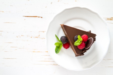 dessert: Chocolate cake slice on white plate mint berries, white background