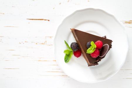 postres: Rebanada de pastel de chocolate en un plato blanco bayas de menta, fondo blanco