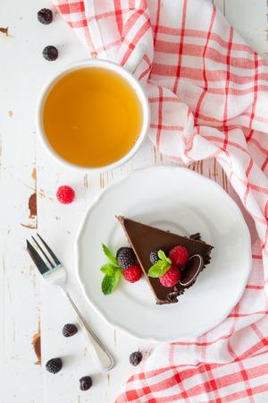 De cakeplak van de chocolade op de bessen van de witte plaatmunt, witte achtergrond