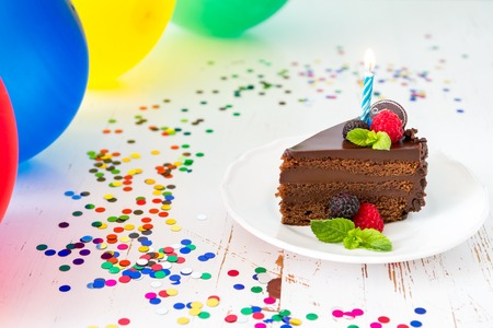 Birthday chocolate cake with candle, light blue background, bokeh Stock Photo