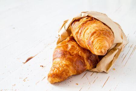 fresh leaf: Croissants in paper bag, white wood background