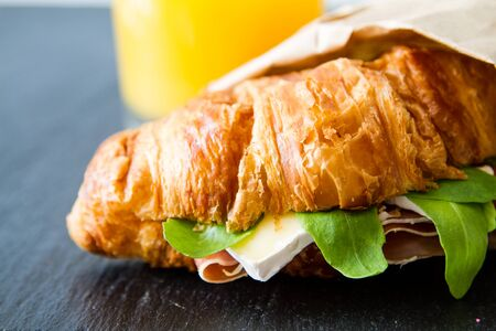 brie: Sandwich croissant with ham brie arugula white wood background Stock Photo