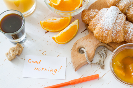 breakfast: Desayuno nota Buenos días - cruasanes café mermelada naranjas fondo de madera blanca Foto de archivo