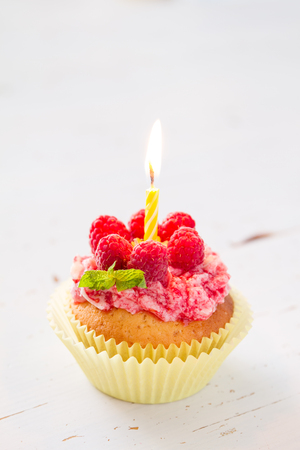 party food: Birthday cupcake with raspberry and candy,white wood background