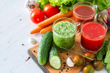 Selectie van groenten en sap, hout witte achtergrond