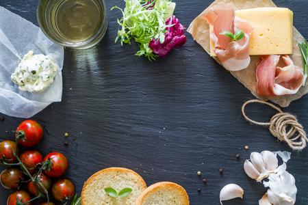 jamon y queso: ingredientes de sándwich en el fondo de piedra oscura, vista desde arriba
