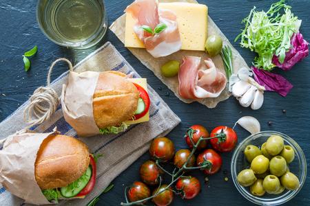 haciendo pan: Sandwich ingredients on dark stone background, top view Foto de archivo