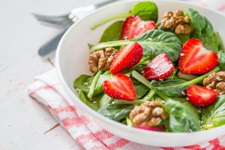 Strawberry salad in white bowl, white wwod background, copy space, closeup