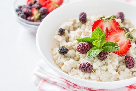 comidas saludables: Desayuno - harina de avena con miel y bayas, taz�n azul, el fondo de madera blanca Foto de archivo