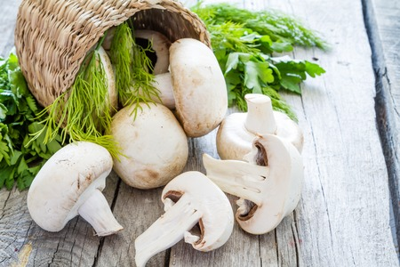 Raw mushrooms in basket, copy space, rustic wood background Banque d'images