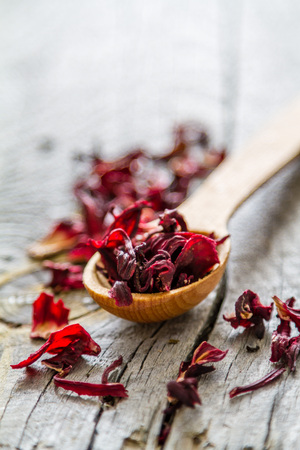 Dry hibiscus tea in wood spoon, rustic wood background