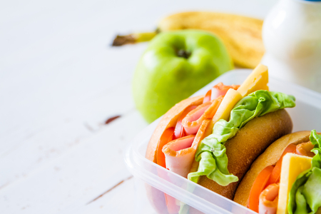 Lunch box with sandwich salad and friuts, white wood background