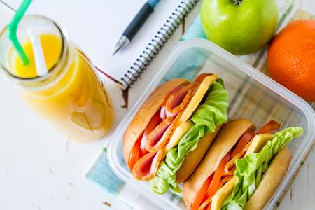 bocadillo: Rectángulo de almuerzo con ensalada de sandwich y friuts, la madera de fondo blanco, vista desde arriba Foto de archivo