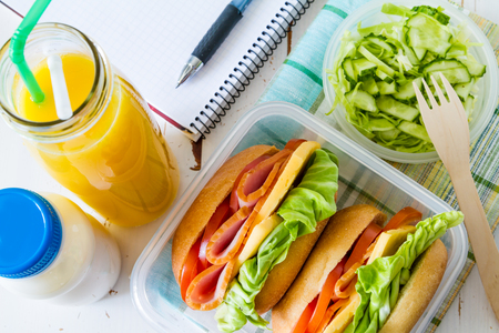 Lunch box with sandwich salad and friuts, white wood background, top view