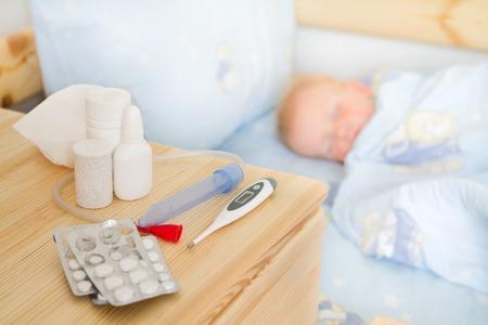 enfant malade: Soins de sant� - m�dicaments et des tissus avec un b�b� malade dans son lit