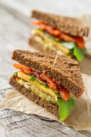 bocadillo: Sándwich vegano con ensalada y queso, en el fondo de madera rústica, copia espacio Foto de archivo
