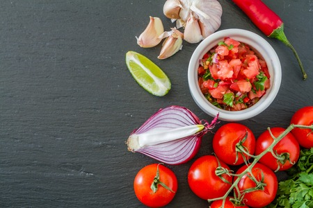 red chili: Salsa sauce and ingredients, dark stone background Stock Photo