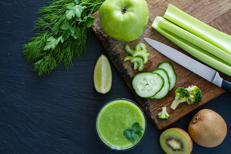 green vegetables: Green smoothie and ingredients, dark stone backgroun, top view, copy space