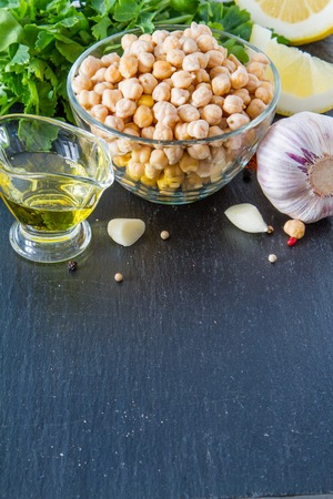 hummus: Hummus ingredients, dark stone background, copy space