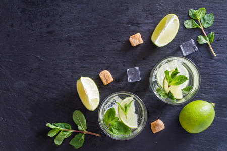 fruit in water: Mojito and ingredients, dark stone background, top view