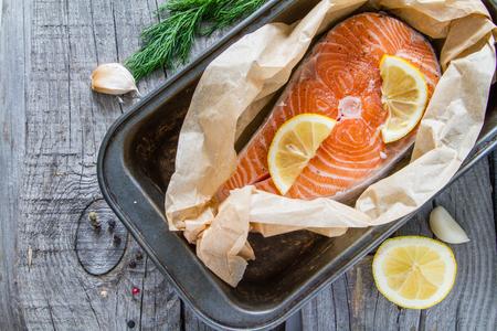 fresh fish: Salmon steak and ingredients, rustic wood background