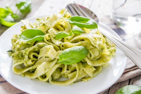 green herbs: Pesto pasta on white plate, rustic wood background