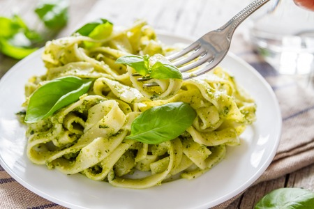 Pesto pasta on white plate, rustic wood background Stock Photo - 48448895