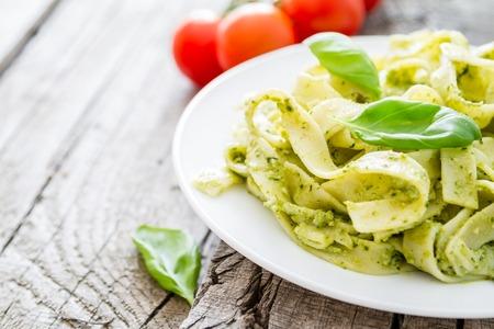 Pesto Pasta auf weißem Teller, rustikale Holz Hintergrund
